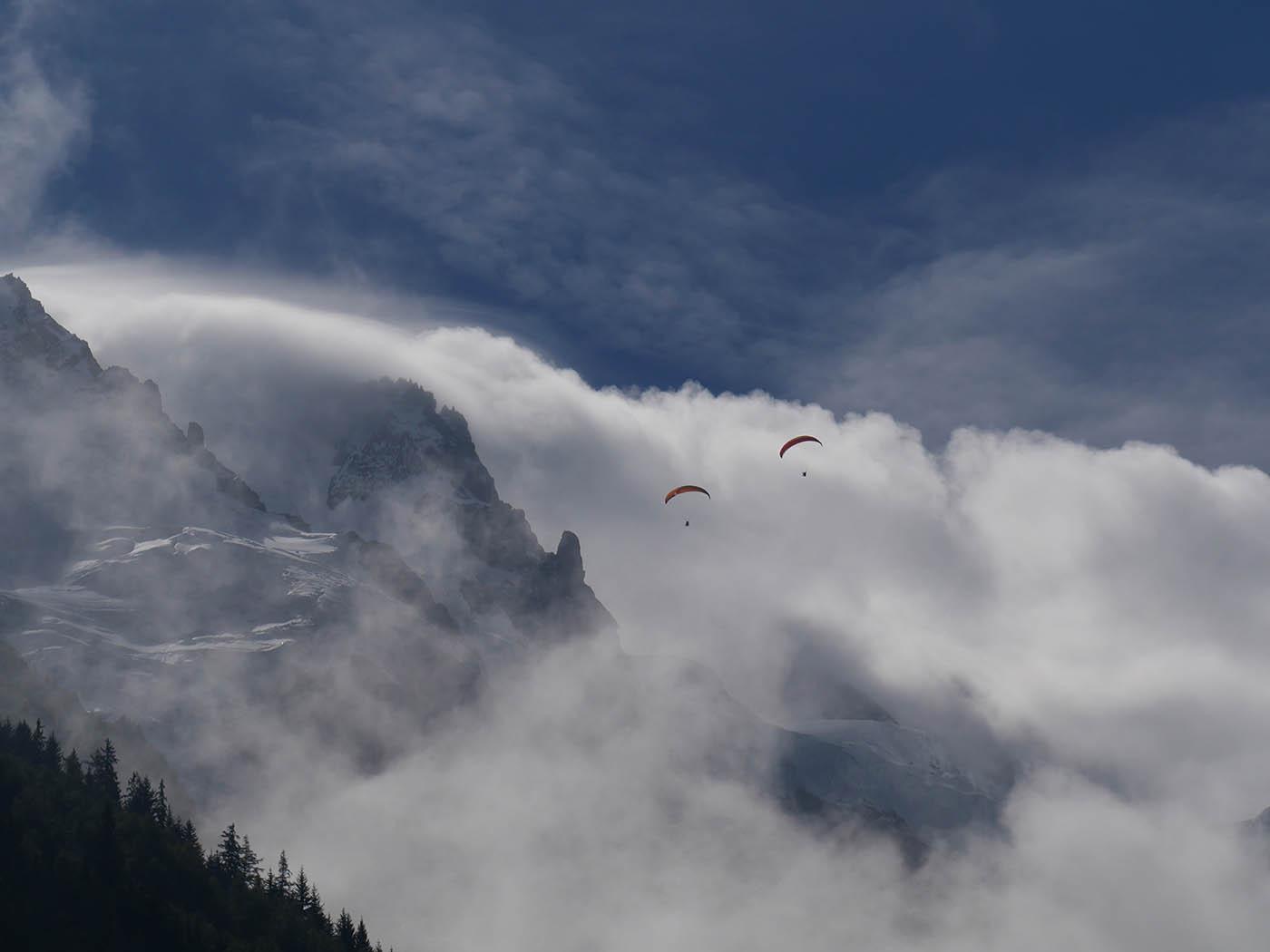 photo paysage montagne avec parachutes dans les nuages